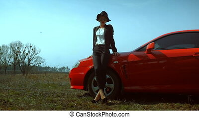 lady on high heels stands with a red sports car - sexy lady...