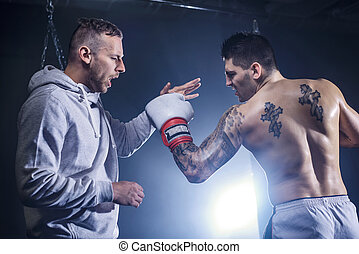 Coach with boxer sparring on the gym