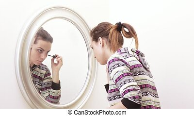 Girl paints face at mirror - At the mirror the girl puts on...