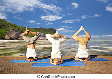 people making yoga headstand on mat outdoors - fitness, yoga...