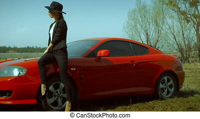woman on high heels sits on a red sports car - hot elegant...