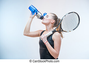 woman drinking water - young woman in tennis uniform with...