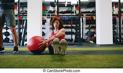Senior woman working out her abs with medicine ball. -...