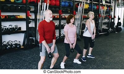 Fit seniors in gym working out, doing squats with...