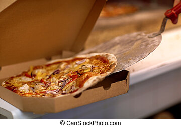chef placing pizza from peel to box at pizzeria - food,...