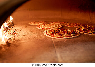 pizza baking in oven at pizzeria - food, italian kitchen and...