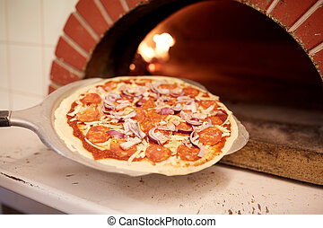 peel placing pizza into oven at pizzeria - food, italian...