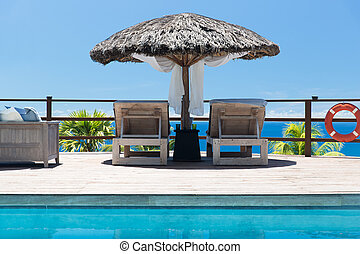 palapa and sunbeds at seaside swimming pool - travel,...