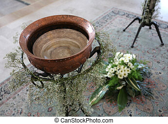 Small baptismal font in copper decorated with flowers during...