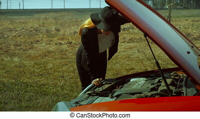 business lady looks under the hood of a broken car - young...