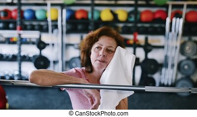 Senior woman in gym resting, wiping sweat with towel -...