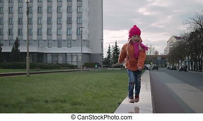 a little girl walks through the city
