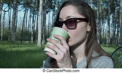 A girl in glasses arranged a lunch in the park. He drinks...