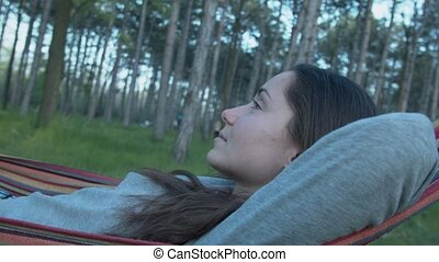 A beautiful girl is resting in the park on a hammock. Young woman lying in a hammock in garden