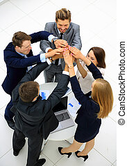 Group of business people celebrating their teamwork with a high