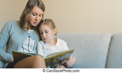Mother and daughter reading a book.