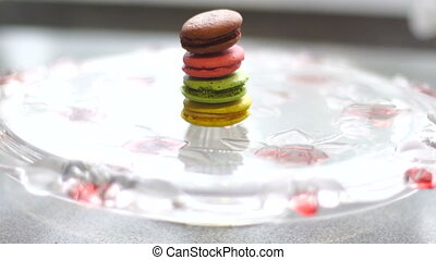 girl finger pushes macaroon cookies and its falls on a plate