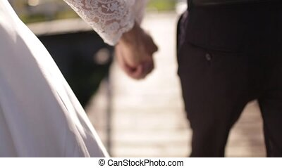 the groom holds the bride's hand in the summer