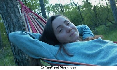 Beautiful happy young woman on a hammock in the park smiling. In the shade of the trees, a girl resting swaying on a hammock.
