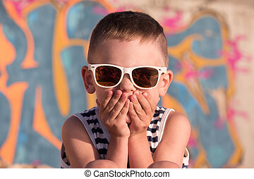 cute little boy wearing sunglasses closed his mouth with...