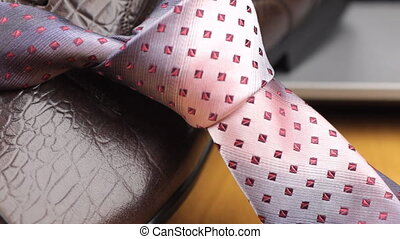 Video of red tie on men's shoes. Dolly shot. Close-up....