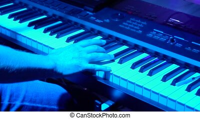 musician playing the electronic piano to a rock concert....