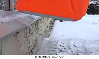 man clean with large shovel snow from sill in winter time. 4K