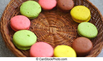 girl takes yellow biscuits macaroon from plates - close up...
