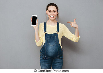 Happy pregnant woman pointing finger at blank screen mobile...