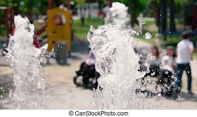Children defocused having fun on background of clear water fountain