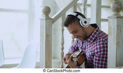 Happy attractive man sitting on stairs with wireless headphones study playing acoustic guitar at home