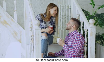 Young happy and loving couple drink tea and talking while sitting on stairs in living room at home