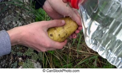hands of a young man wash the potatoes outdoors,water bottle