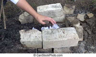 hand building a grill out of bricks