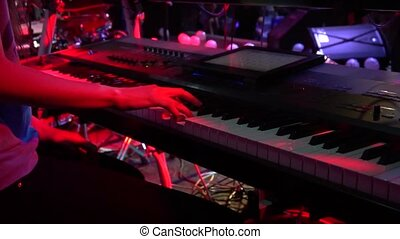 Girl is playing a synthesizer at a rock concert close up