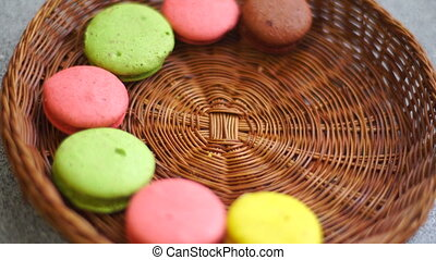 multi-colored macaroon cookies in the wicker plate close up