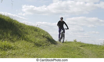 Man Riding Bicycle up Mountain Grass Hill - Young sports man...