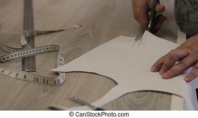 Designer cuts a template for the dress of white leather. tracking shot. in slow motion
