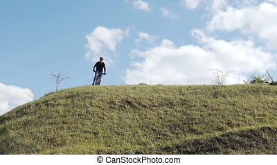 Man Riding Bicycle on Top of Town - Young sports man wears...