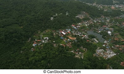 Aerial view of rural houses in the green mountain of Phuket...