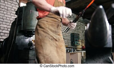Blacksmith in forge - handles hot incandescent piece of...