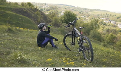 Biker Resting on the Top - Young sports man resting on the...
