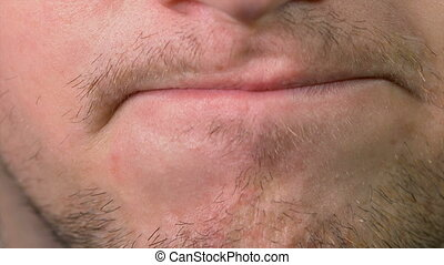 Close up of young annoyed man mouth and lips expressing...