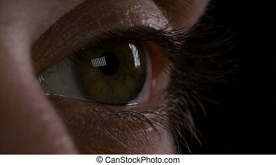 Macro of young man eye blinking in the dark