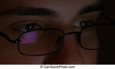 Closeup of teenager eyes wearing glasses and browsing internet on tablet pc in a dark room