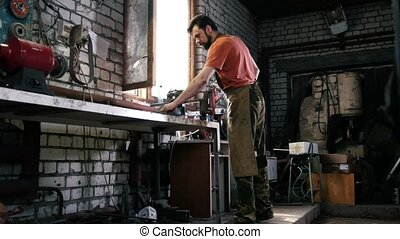 Blacksmith in forge - sharpening iron tools with sparkles -...