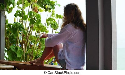 The girl sits on the terrace and looks towards the sea - The...