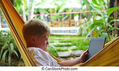 young guy playing on laptop lying in a hammock - guy playing...