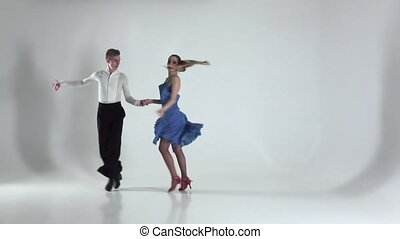 Couple is dancing salsa on white background, shadow. Slow...