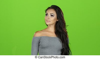 Brunette woman in gray sweater posing on camera, green screen